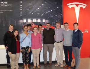 Nichols College students stand in front of Tesla sign